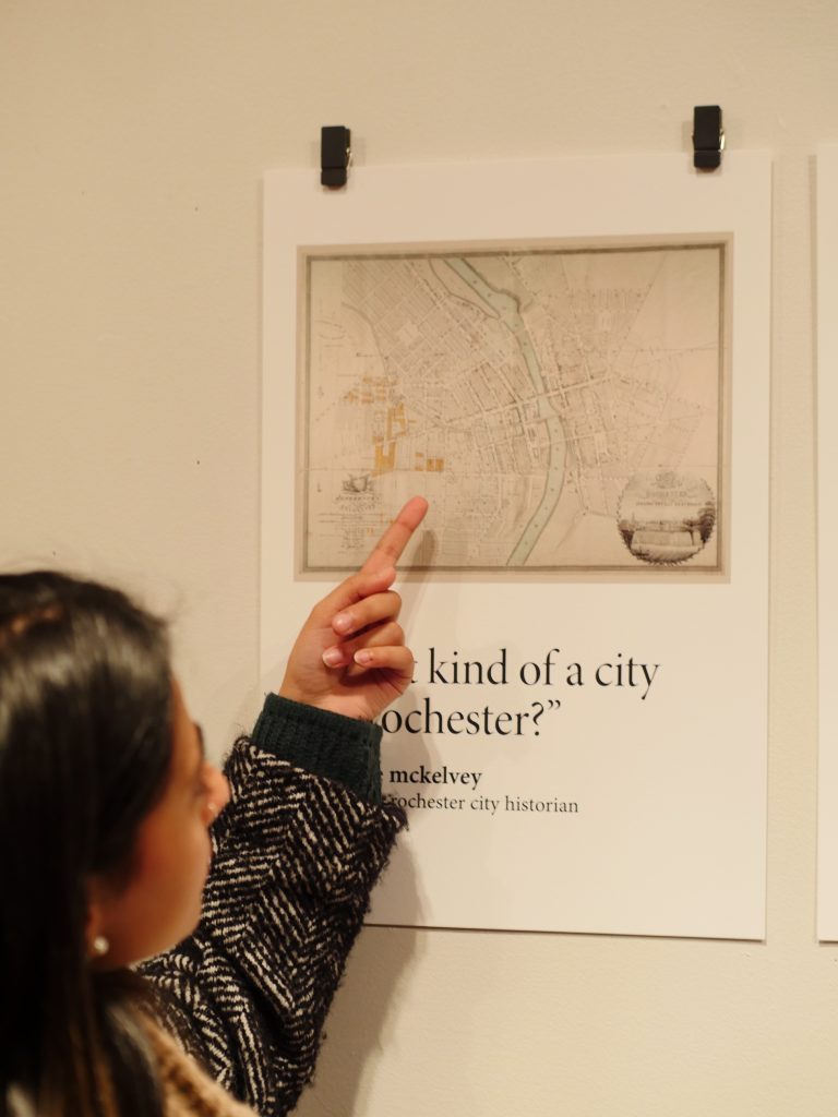 a gallery visitor points to a print featuring an old map of rochester