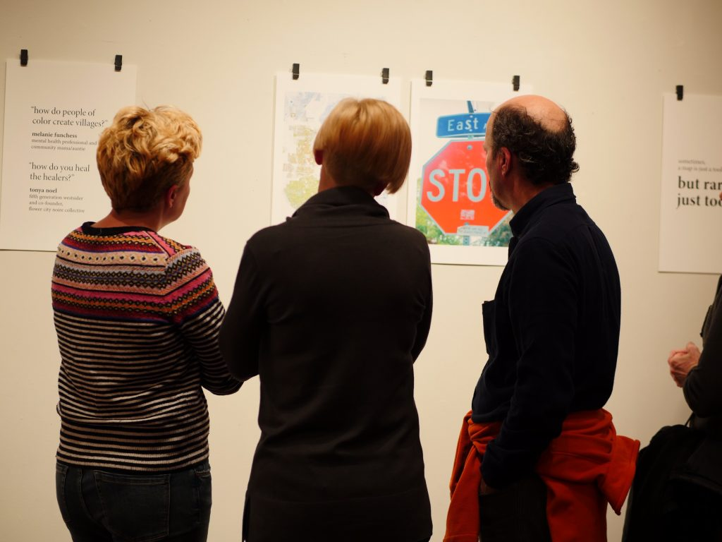 three gallery visitors examine prints