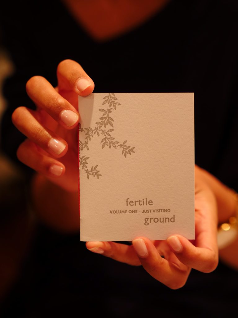 kate holds a copy of volume one of the fertile ground zine: a passport-sized light gray book with leaves and text on the cover, bound with red thread