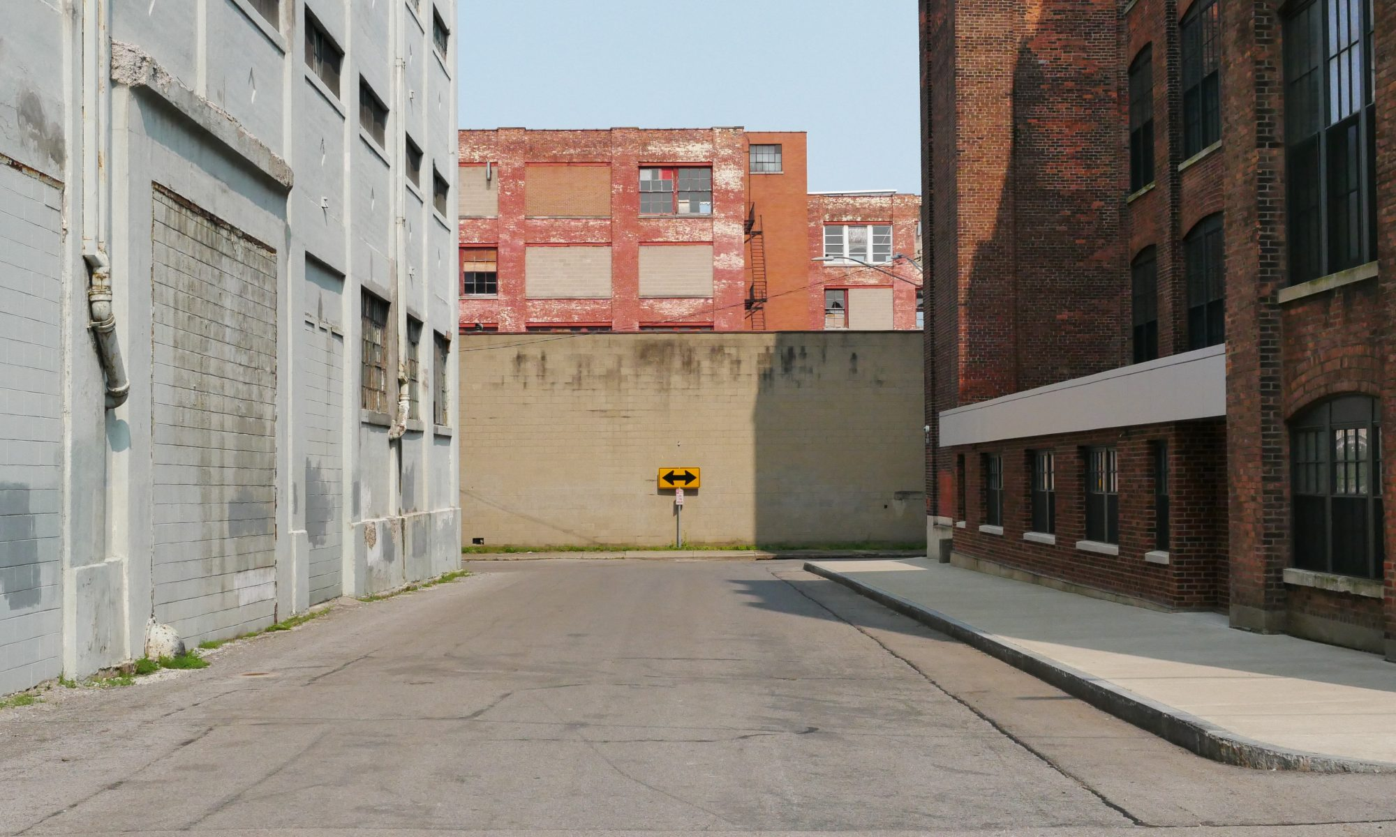 an urban street dead-ends between two warehouse buildings