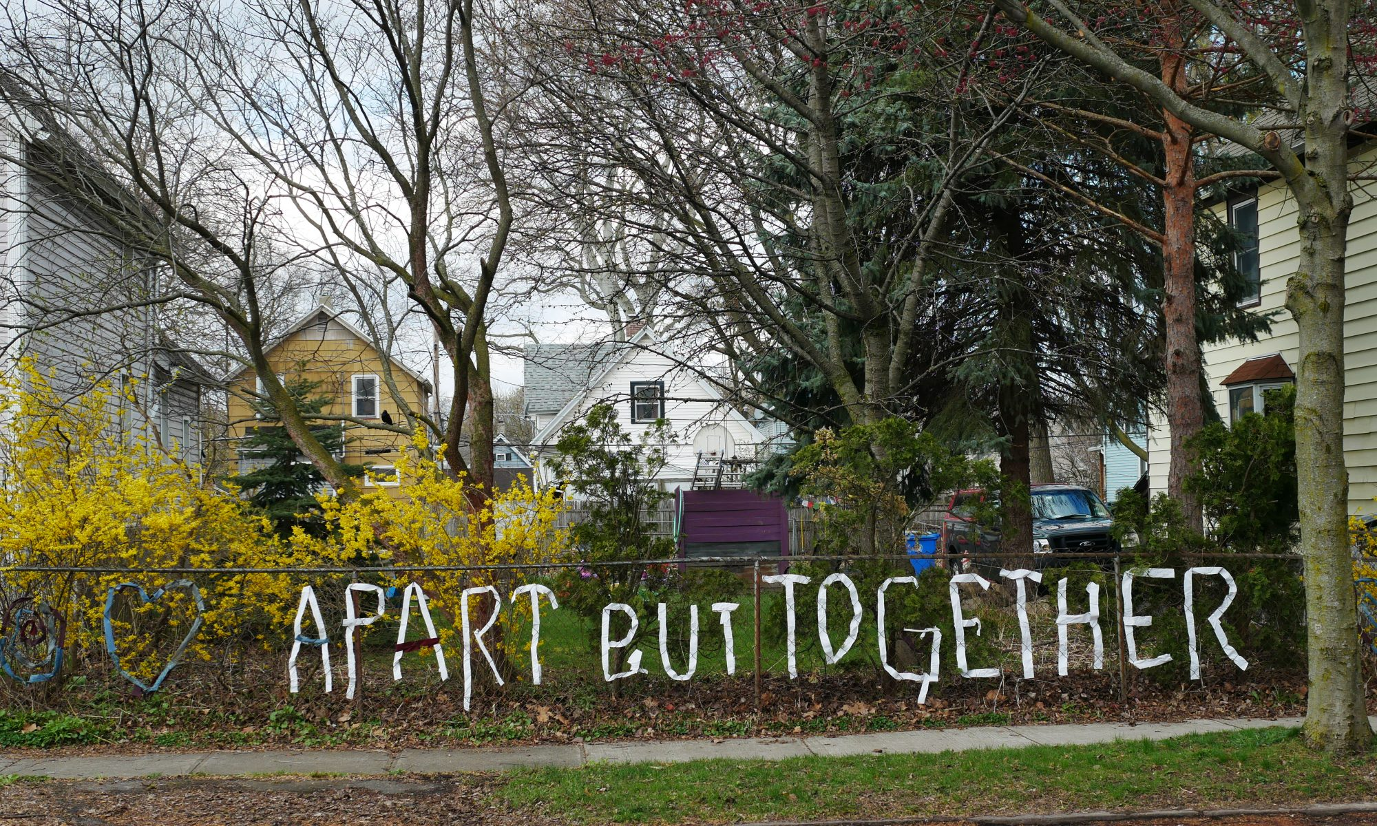 "white ribbon threaded onto a chainlink fence to spell out ""apart but together"""