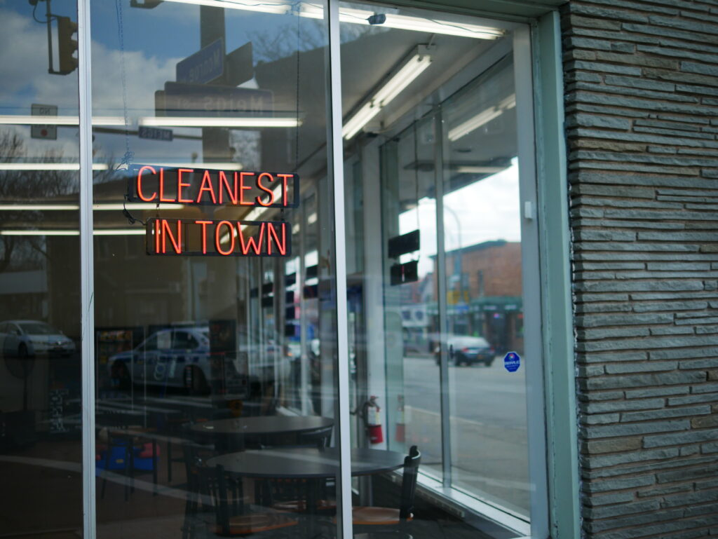 "a neon sign in a laundromat window reads ""cleanest in town"""