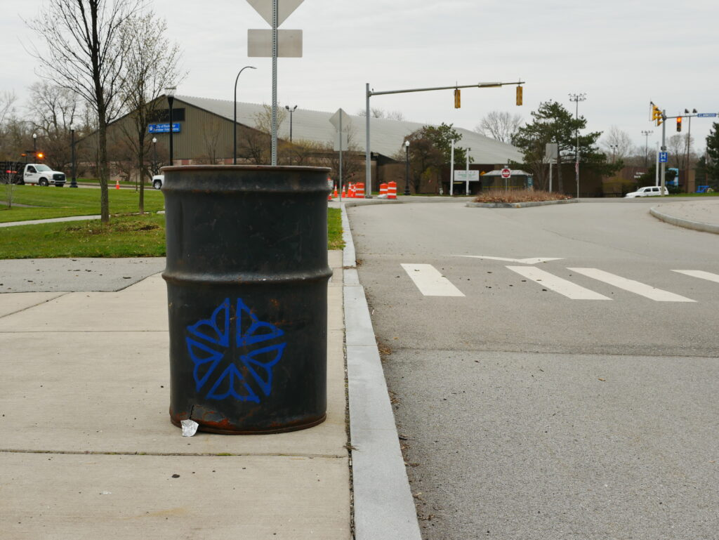 a black trash can with the rochester logo on a city sidwalk