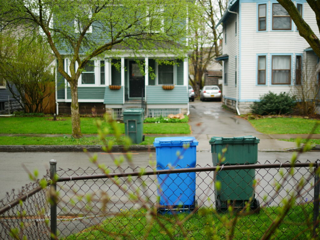 residential garbage and recycling bins sit on a curb like old friends