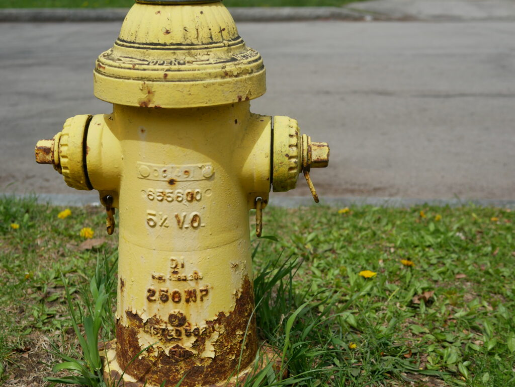 a faded and rusty yellow fire hydrant
