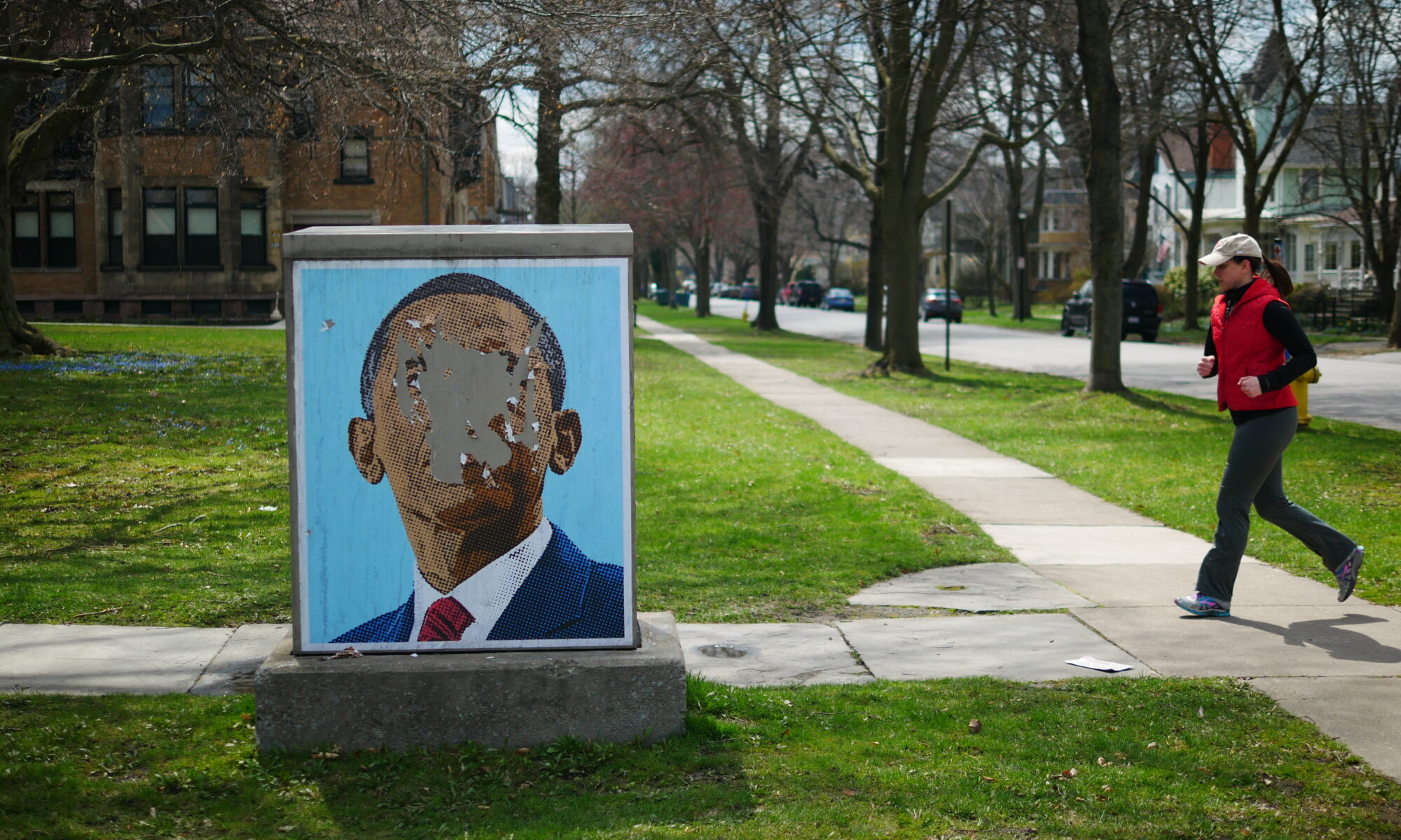 a jogger runs by a defaced image of barack obama